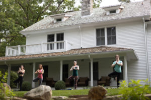 ladies yoga wellness retreat with ladies doing yoga in backyard