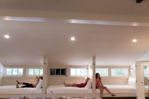 three girls lounging on bunk beds in bunk room
