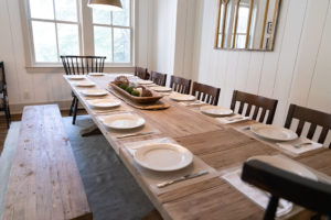 banquet sized table in dining area with plates and silverware