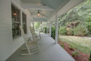 wrap around porch with rocking chairs in front of Fairview House