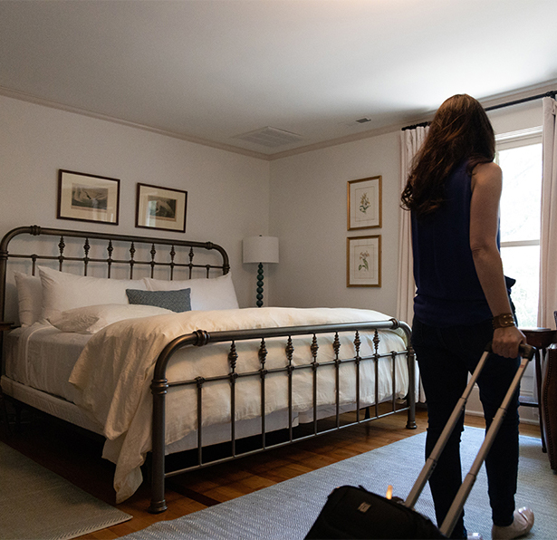 Bedroom at Fairview House with lady walking in with suitcase