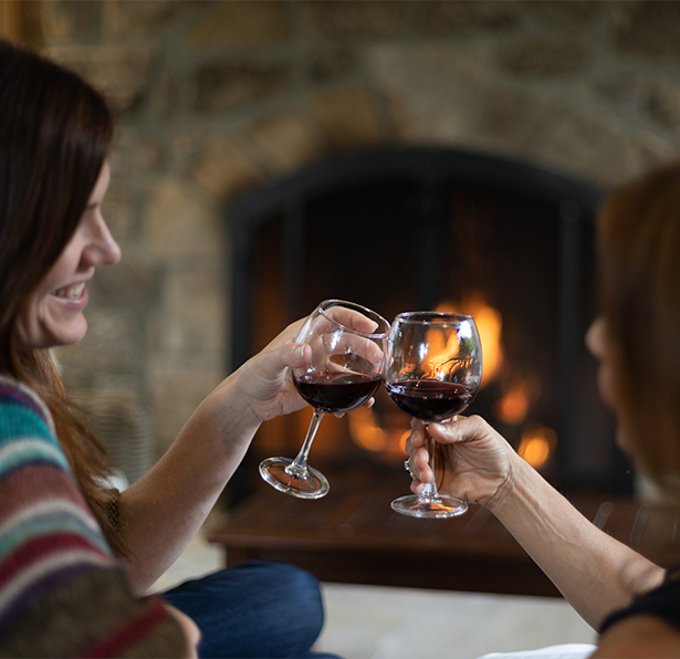 Ladies lounging on the back patio of Fairview house in front of fireplace with wine glasses