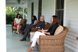 group of ladies and man chatting in chairs on wrap around porch drinking champagne